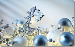 Silver and blue ornaments amongst fairy lights